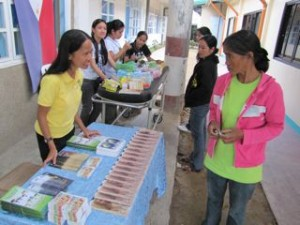 Missionary Minnie greets a patient at the couseling-literature booth at a medical mission in Mayoyao
